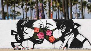 Graffiti by artist Pony Wave depicting two people kissing while wearing face masks, Venice Beach, California, USA - March 2020