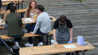 A worker disinfects a recently vacated table outside a re-opened pub in Newcastle
