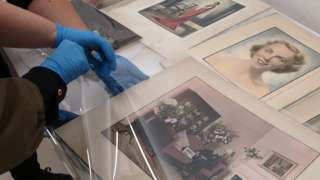 Taking a photographic print by E. Chambre Hardman out of its protective sleeve