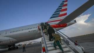 Pessoas embarcando em avião com bandeira americana estampada na parte traseira