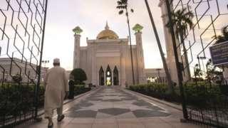 A Muslim man walks inside the Sultan Omar Ali Saifuddien mosque to perform the sunset prayer in Bandar Seri Begawan