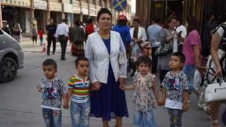 """This file photo taken on June 4, 2019 shows a Uighur woman waiting with children on a street in Kashgar in China""""s northwest Xinjiang region."""