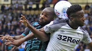 Aldo Kalulu of Swansea City (L) challenges Florian Jozefzoon of Derby County in the air