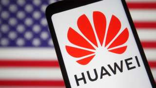 The Huawei logo on a smartphone in front of a blurred US flag