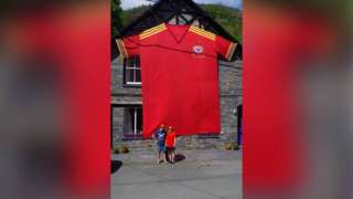 the giant shirt hanging on the front of the house