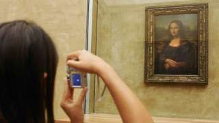 Woman taking a photo of Mona Lisa in the Louvre
