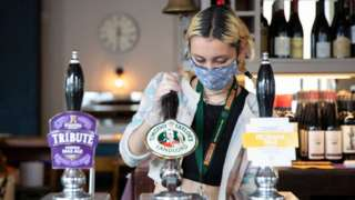 A woman working in a pub, wearing a mask
