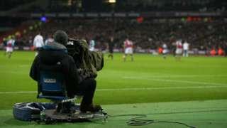 A cameraman films a Premier League game