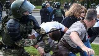 Policial paramentado com capacete e coletes bate em manifestantes com roupas comuns