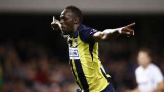 Usain Bolt spreads his arms wide to celebrate scoring a goal