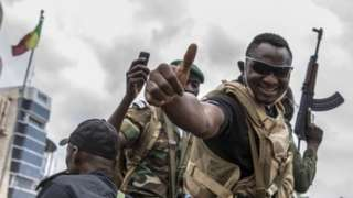 A Malian soldier gives the thumbs up as civilians cheer military and police as they drive through the streets of Bamako, a day after the military seized the Presidency in Bamako, Mali, 19 August 2020.