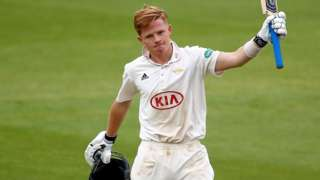 Ollie Pope raises his bat in his left hand in celebration after making a century against Yorkshire