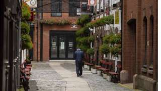 A man walks down Commercial Court in Belfast