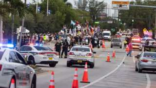 Police at the scene after a car drove into a Pride parade in Florida, June 2021