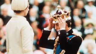 Prince Charles is given the gold coronet of the Prince of Wales by his mother Queen Elizabeth