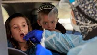 Duas crianças aparecem dentro do carro, uma delas com coleta de material do nariz para teste, feita por profissional de saúde que aparece de costas