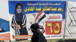 An Iraqi woman walks next to election campaign posters for candidates in Baghdad, Iraq (5 October 2021)