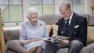 Queen and Prince Philip looking at a card from the Duke and Duchess of Cambridge's children