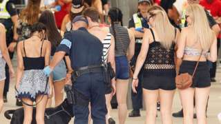 A police officer uses a sniffer dog to test festival goers in Melbourne