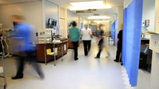 Nurses and other hospital staff are walking around a hospital ward.