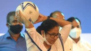 পশ্চিমবঙ্গের মুখ্যমন্ত্রী মমতা ব্যানার্জী হাতে একটি ফুটবল নিয়ে ছুঁড়ছেন