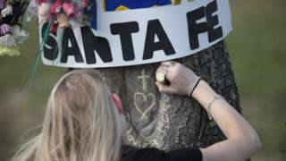 Student chalks a message on a tree outside Santa Fe High School, TX 19 May 2108