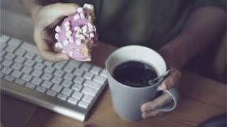 Teclado e duas mãos segurando uma rosca doce e um café