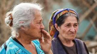 Women by destroyed house in Azerbaijan