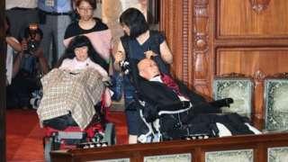 Funago ve Kimura, tekerlekli sandalyeleriyle salona girdiğinde alkışlarla karşılandı.
