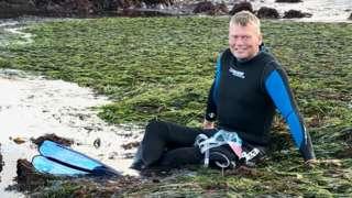 Tom Heap sat in seagrass