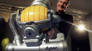 Sir James Dyson holds up a vacuum cleaner