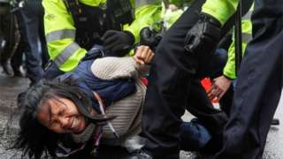 An anti-lockdown protester is arrested by police officers