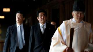 """Japan""""s Prime Minister Shinzo Abe (C) is led by a Shinto priest as he visits Yasukuni shrine in Tokyo December 26, 2013"""