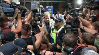 Cardinal George Pell is swarmed by media as he leaves a court in February