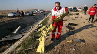 Red Crescent workers check the debris from the Ukraine International Airlines plane,