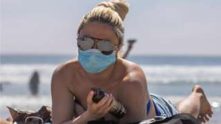 A woman wearing a face mask sunbathes on the beach amid the novel coronavirus pandemic in California, 25 April 2020