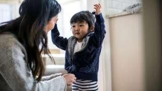 """妈妈为孩子挑选衣服这样的家务事就是""""母亲把关""""的例子,这是一种视为需由妈妈来操持的细微家务(Credit: Getty Images)"""