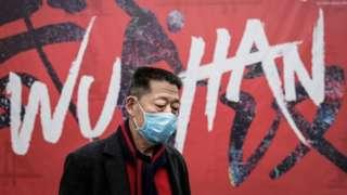 Un hombre frente a un mural que dice Wuhan