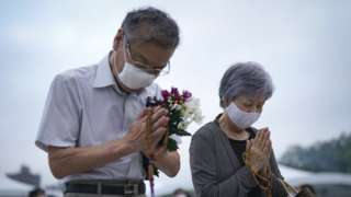 An elderly couple prays for victims in front of a cenotaph at Peace Memorial Park in Hiroshima