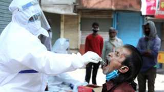 An Indian doctor takes samples from a worker during COVID-19 routine testing at a local market on May Day