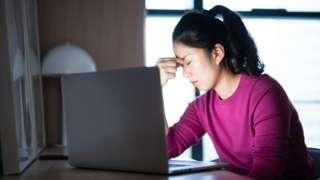 疲惫的女员工在电脑前揉眼睛