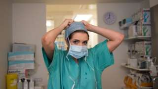 Nurse putting on a surgical mask