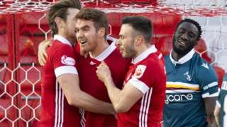 Ash Taylor and Andrew Considine celebrate with Tommie Hoban (centre)