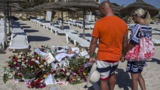 Tourists look at flowers on Tunisia beach