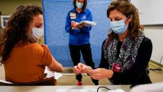 Healthcare workers take part in a rehearsal for the administration of the Pfizer coronavirus vaccine