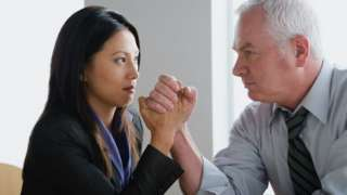 A woman and a man arm wrestling in the office