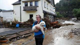 A man and his dog look at the damage caused by flooding in Germany, July 2021