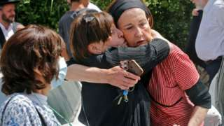 An Ultra-Orthodox Jewish woman comforts another at a cemetery in Benei Brak, 30 April