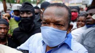 """Yves Jean-Bart, president of the Haitian Football Federation, wearing a protective face mask arrives at his hearing at the Crois-Des-Bouquets prosecutor""""s office"""