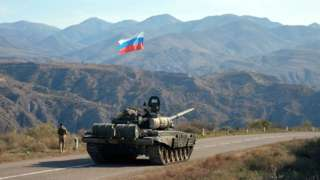 A service member of the Russian peacekeeping troops walks near a tank near the border with Armenia